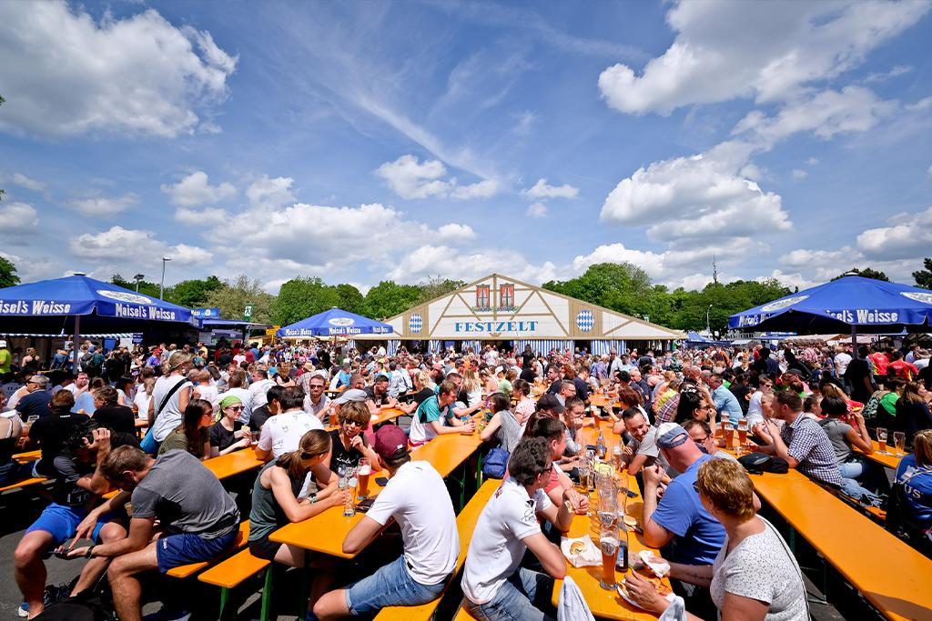 Menschen an Bierbänken vor dem Festzelt in der Übersicht